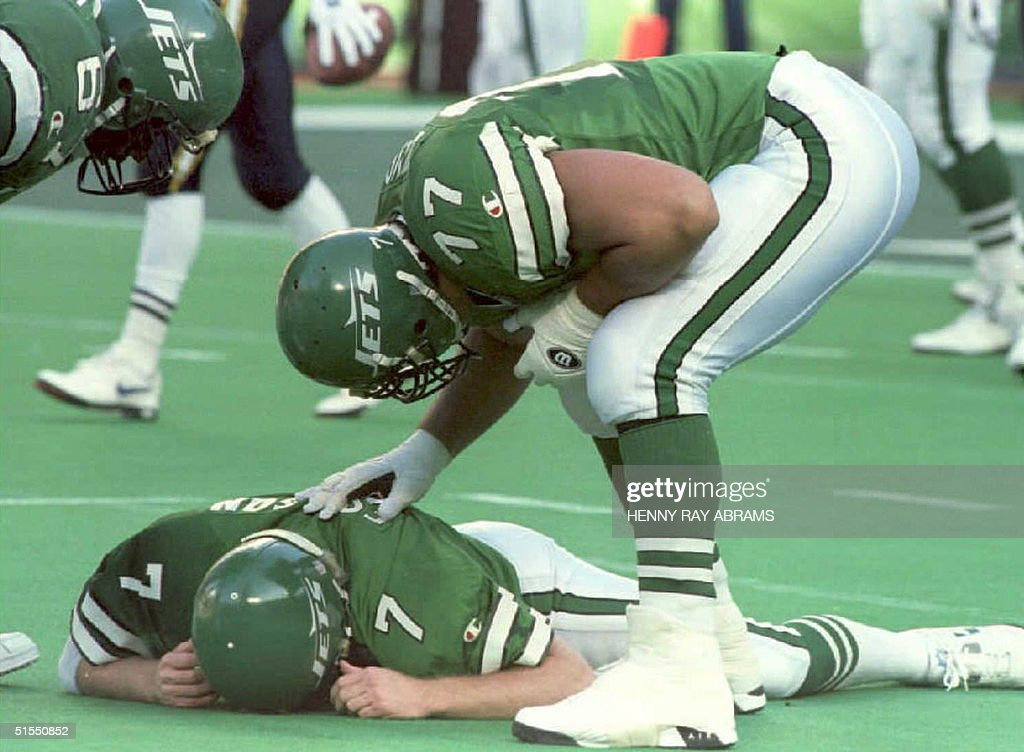 New York Jets' Matt Willig (R) and Dwayne White (L) check on their quarterback Boomer Esiason who was knocked down, and suffered a concussion, after throwing an incomplete pass in the second quarter at Giants Stadium 18 December 1994. Esiason had to leave the game and was replaced by Jack Trudeau.