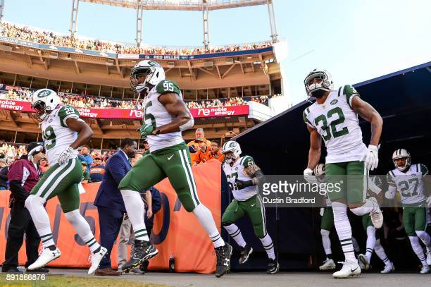 New York Jets players including Bilal Powell Josh Martin and Juston Burris run onto the field before a game against the Denver Broncos at Sports...
