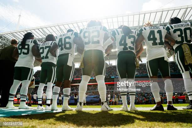 New York Jets players link arms during the national anthem prior to their game against the Miami Dolphins at Hard Rock Stadium on November 4 2018 in...