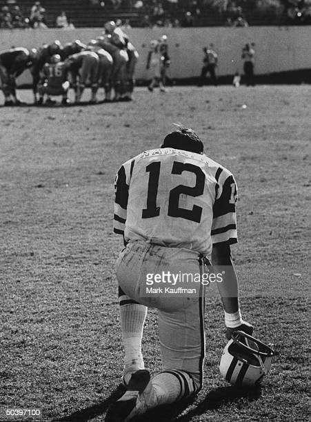 New York Jets quarterback Joe Namath kneeling on the sidelines during a game against the Houston Oilers