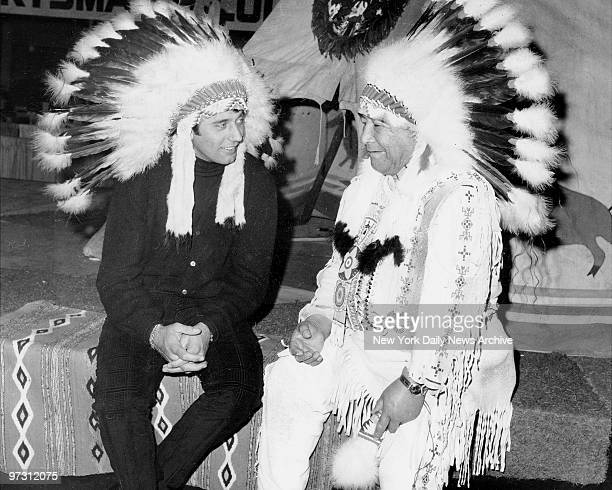 New York Jets' quarterback Joe Namath who'll soon undergo operation on left knee tries on chief's bonnet a gift of Chief Brown Horse who has tepee...