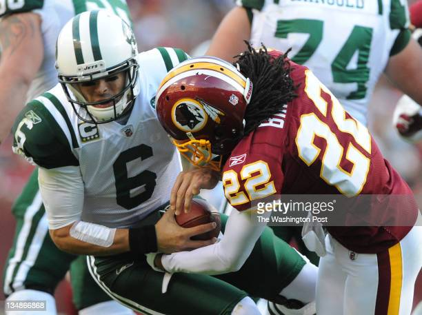 New York Jets quarterback Mark Sanchez goes down as Washington Redskins defensive back Kevin Barnes tries to stip the ball in the fourth quarter of...
