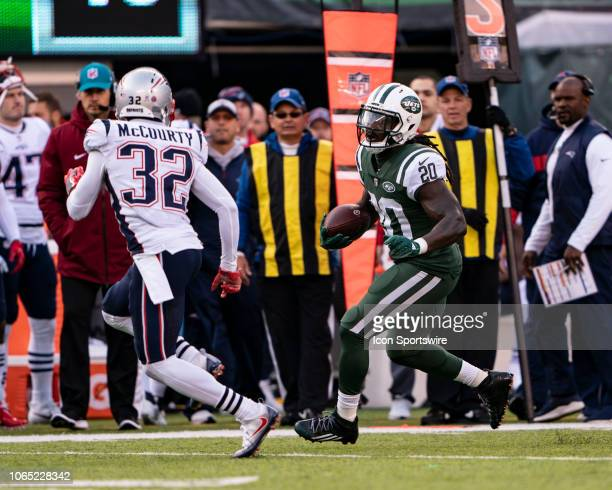 New York Jets Running Back Isaiah Crowell runs with the ball with New England Patriots Safety Devin McCourty in pursuit during the second half of the...