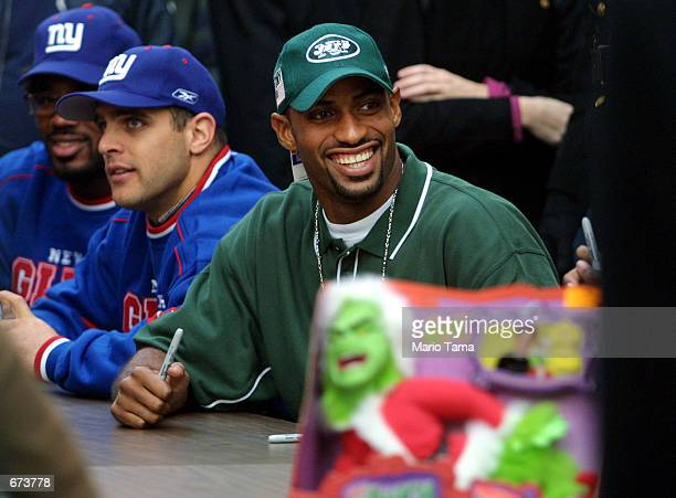 New York Jets safety Chris Hayes smiles while signing autographs as New York Giant players Dhani Jones and Greg Comella look on during a toy drive to...