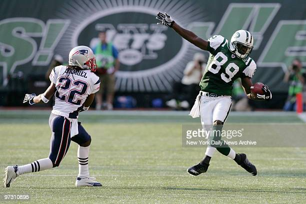 New York Jets' wide receiver Jerricho Cotchery catches a pass while defended by New England Patriots' Asante Samuel during a game at Giants Stadium...