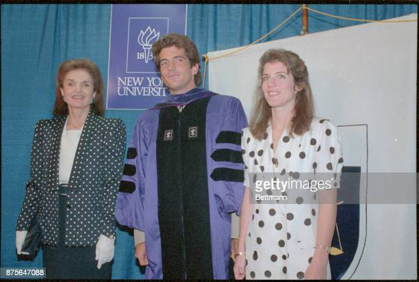 John F Kennedy Jr is flanked by his mother Jacqueline Onassis and his sister Caroline Schlossberg during a photo session following his graduation...