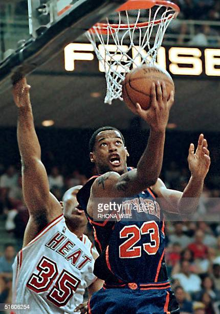 New York Knick forward Marcus Camby charges past the defense of Miami Heat forward Clarence Weatherspoon during third period action 25 April at the...