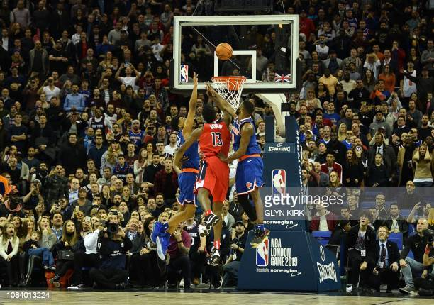 TOPSHOT New York Knicks' Allonzo Trier and New York Knicks' Emmanuel Mudiay jump against Washington Wizards' Thomas Bryant resulting in a goal...