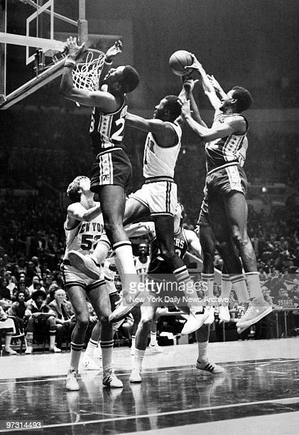 New York Knicks' Bob McAdoo is sandwiched by Philly's Joe Bryant and Harvey Catchings as he goes up for a shot