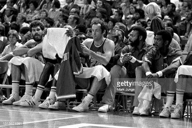 New York Knicks forward Bill Bradley puts on his warmup jersey as he sits on the bench during an NBA basketball game against the Denver Nuggets at...