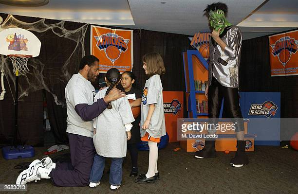 New York Knicks Head coach Don Chaney talks with some children as Knicks' rookie center 7'5 Slavko Vranes plays the part of Frankenstein in a skit...