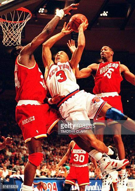 New York Knicks' John Starks drives to the basket between Houston Rockets' Hakeem Olajuwon and Robert Horry during the third quarter of Game four of...