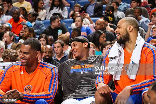 New York Knicks players from left Kurt Thomas Carmelo Anthony and Tyson Chandler share a laugh on the bench as their teammates play in the fourth...
