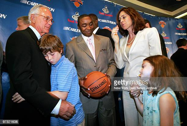 New York Knicks' president Isiah Thomas smiles as Larry Brown hugs his 11-year-old son, L.J., while Brown's wife, Shelly, and daughter Madison look...