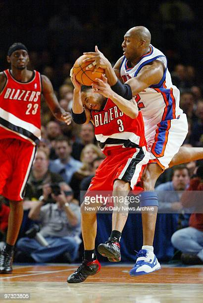New York Knicks' Vin Baker grabs the ball away from the Portland Trail Blazers' Damon Stoudamire as Trail Blazers' Darius Miles looks on during...