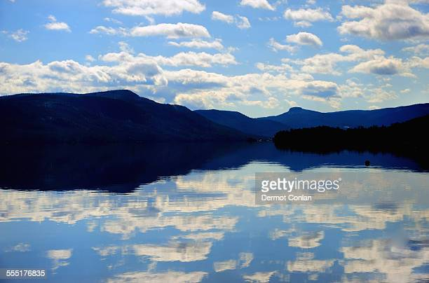 usa, new york, lake george, symmetrical view of blue sky and clouds reflecting in lake - lake george new york stock pictures, royalty-free photos & images