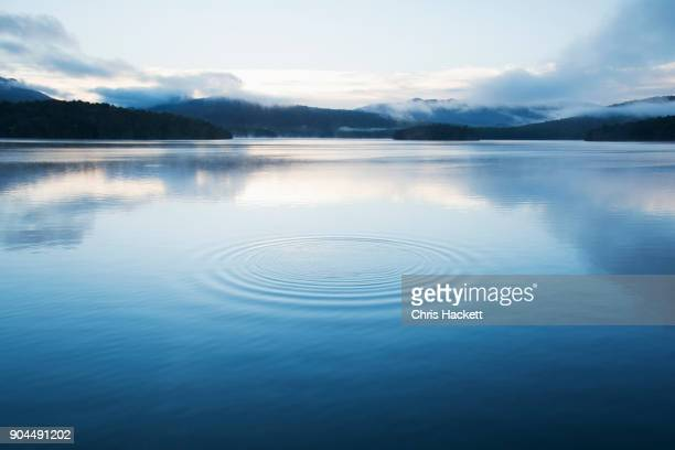 new york, lake placid, circular pattern on water surface - kalmte stockfoto's en -beelden