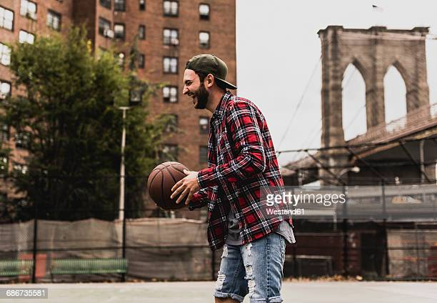 USA, New York, laughing young man with basketball on an outdoor court