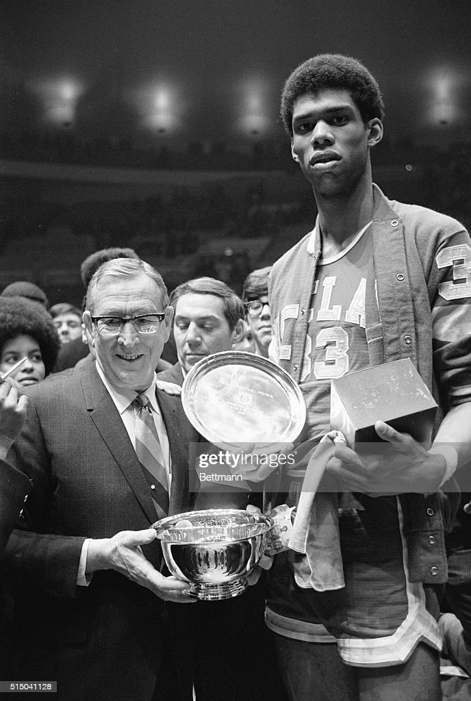 Lew Alcindor shown holding the Most Valuable award over his head, with coach John Wooden of UCLA shown after victory over ST. Johns U.