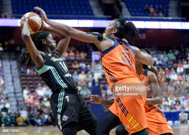 New York Liberty Guard Sugar Rodgers looks to pass as Connecticut Sun Forward Alyssa Thomas defends during the game as the Connecticut Sun host the...