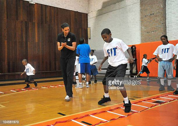 New York Liberty player Nicole Powell cheers on a young participant in the WNBA FIT Clinic sponsored in part with CocaCola on September 30 2010 in...