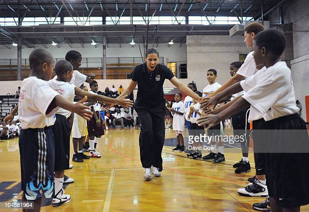 New York Liberty player Nicole Powell slaps hands with participants attending the WNBA FIT Clinic sponsored in part with CocaCola dribbles on...