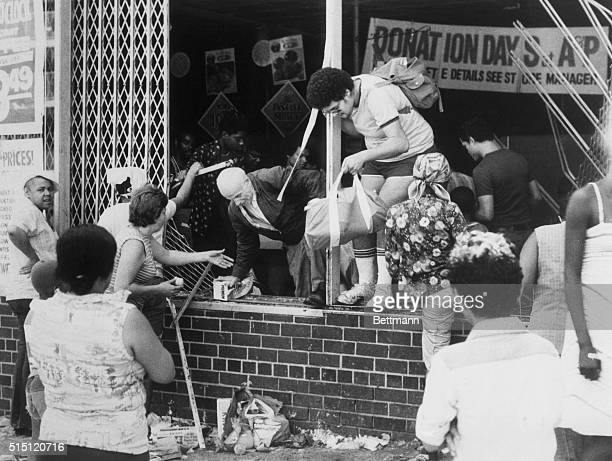 Looters young and old leave an A P supermarket at Ogden Avenue and 166th Street in the Bronx through a broken window as they carry off their stolen...