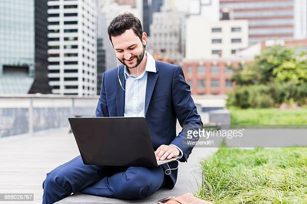 USA, New York, Manager in Manhattan sitting outdoor, using laptop and earphones