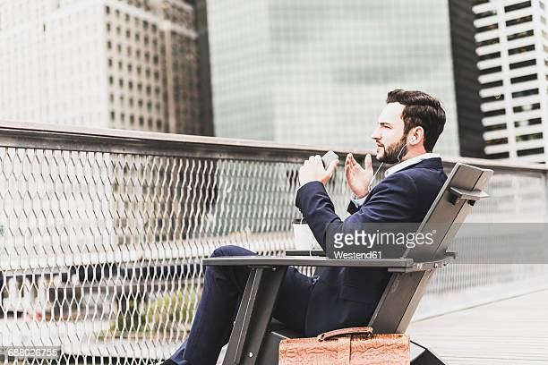 USA, New York, Manager in Manhattan talking on his smart phone, using headphones