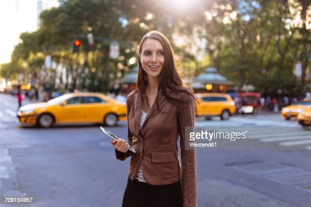 USA, New York, Manhattan, portrait of smiling young businesswoman with tablet on the street