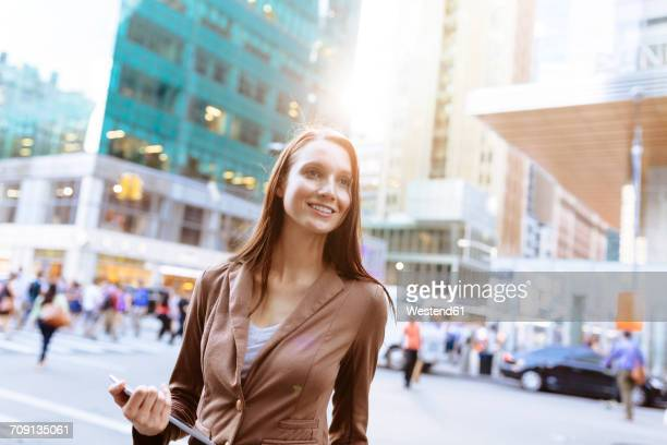 USA, New York, Manhattan, portrait of smiling young businesswoman with tablet