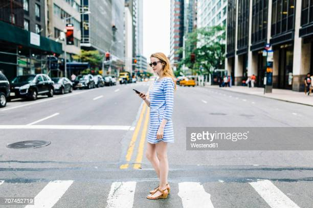USA, New York, Manhattan, Young woman walking in the street, holding mobile phone