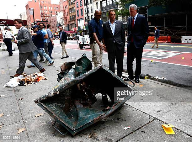 New York Mayor Bill de Blasio and New York Governor Andrew Cuomo stand in front of a mangled dumpster while touring the site of an explosion that...