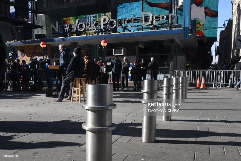 New York Mayor Bill de Blasio(C) makes an announcement during a press conference in Times Square on January 2, 2018 about new barriers to prevent terror attacks and safeguard sidewalks and plazas from vehicles, alongside NYPD Police Commissioner James O'Neill and New York City Department of Transportation Commissioner Polly Trottenberg. /