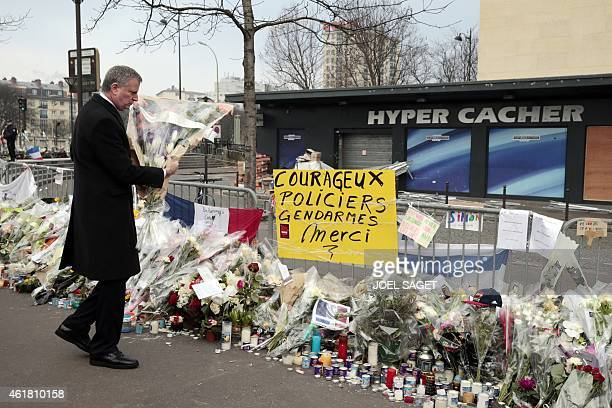 New York Mayor Bill de Blasio places flowers near a sign reading Courageous police gendarmes thank you in front of the Hyper Cacher kosher...