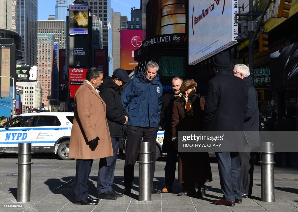 New York Mayor Bill de Blasio(C) stands before a press conference in Times Square on January 2, 2018 about new barriers to prevent terror attacks and safeguard sidewalks and plazas from vehicles, alongside NYPD Police Commissioner James O'Neill and New York City Department of Transportation Commissioner Polly Trottenberg. /