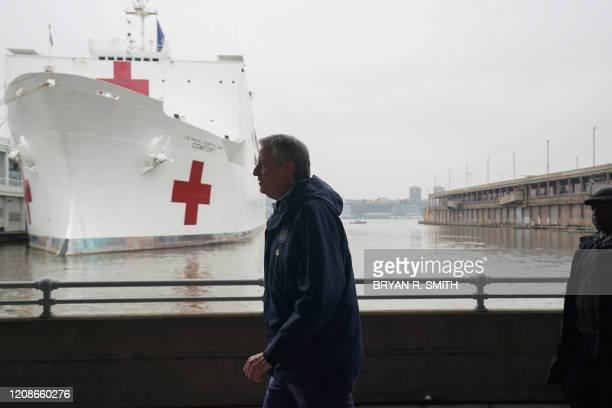 New York Mayor Bill de Blasio walks pat the USNS Comfort hospital ship docked at Pier 90 on March 30 2020 in New York A military hospital ship...