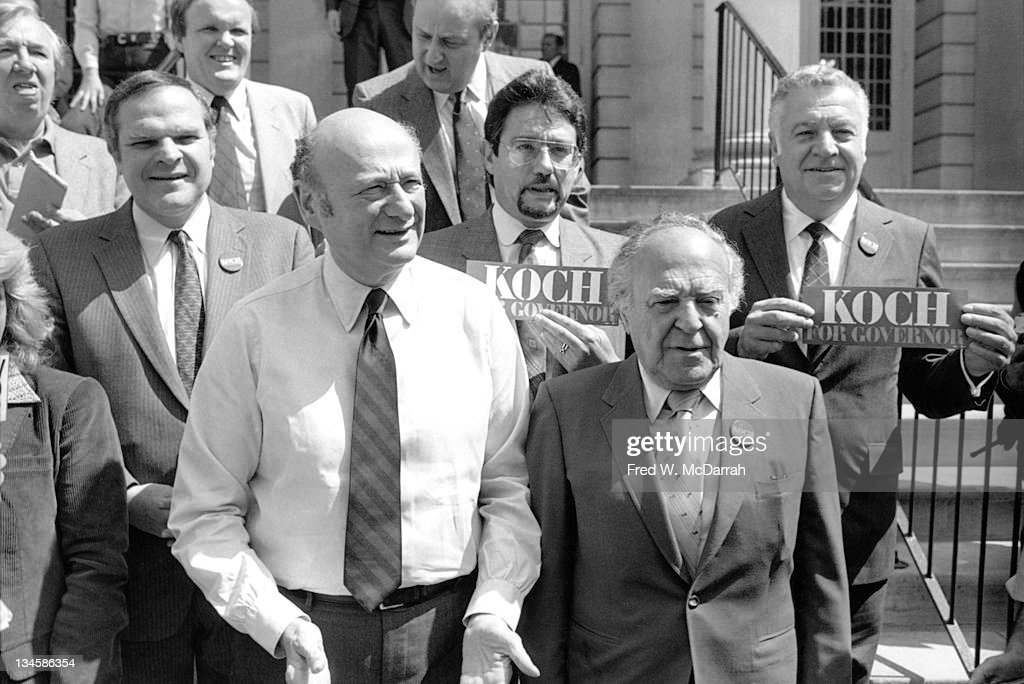 New York Mayor Ed Koch (fore left, in shirt and tie) stands on the steps of City Hall with supporters, among them, Queens borough president Donald Manes (1934 - 1986) (behind Koch's right shoulder), Bronx Democratic Party leader Stanley Friedman (behind Koch's left shoulder, with beard), and leader of Kings County Democratic Party Meade Esposito (1909 - 1993), New York, New York, May 6, 1982.