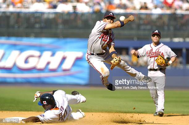 New York Mets' Cliff Floyd is out as he slides into second after breaking up an eighthinning double play as Atlanta Braves' Rafael Furcal make the...