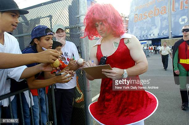 New York Mets' David Wright signs fans' autographs while wearing a dress and red wig during Mets Annual Rookie hazing event following a 32 win over...