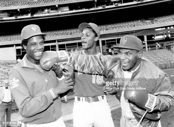 New York Mets' Dwight Gooden laughs off a right from heavyweight Mike Tyson as referee Darryl Strawberry supervises the event at Shea Stadium