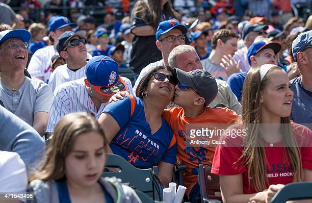 New York Mets fan gives his mom a kiss on the cheek during the game between the Miami Marlins and New York Mets at Citi Field on Sunday April 19 2015...