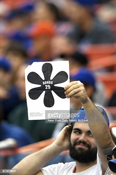 New York Mets' fan heckles San Francisco Giants' Barry Bonds with a sarcastic sign depicting an asterisk during the first game of a doubleheader at...