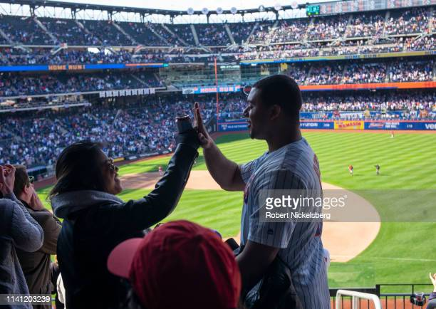 New York Mets fans celebrate a home run by Robinson Cano during a game against the Washington Nationals at Citifield in the Flushing neighborhood of...