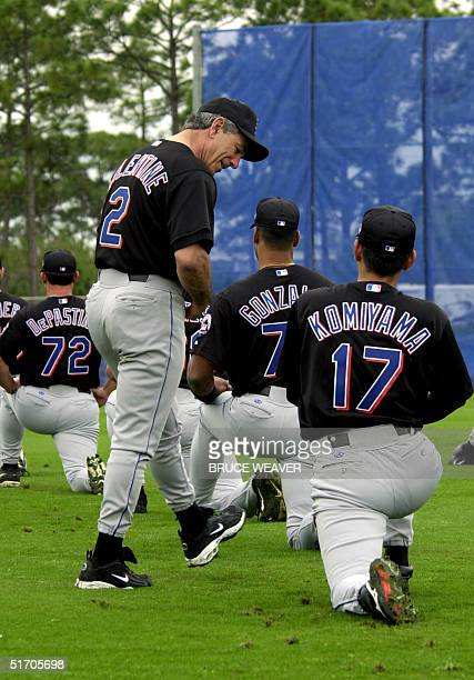New York Mets manager Bobby Valintine watches Japanese pitcher Satoru Komiyama doing stretching exercises 16 February 2002 during the Mets first day...