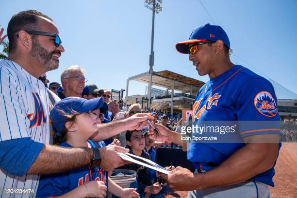New York Mets Manager Luis Rojas signs autographs for fans in the stands during an MLB spring training game between the New York Mets and the Houston...