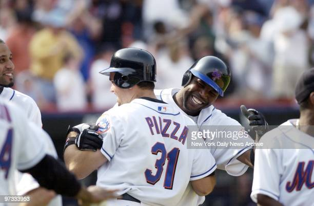 New York Mets' Mike Piazza is hugged by teammate Cliff Floyd after hitting a gamewinning tworun homer in the 10th inning of game against the San...