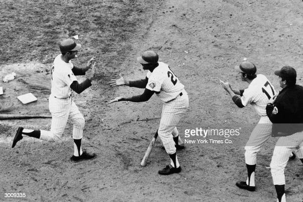 New York Mets outfielders Tommie Agee and Rod Gaspar greet 2nd base player Al Weis after Weis tied the score in the 5th game of the World Series New...