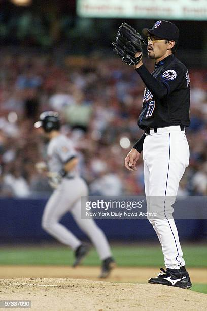 New York Mets reliever Satoru Komiyama after giving up a threerun homer to Houston Astros' Brad Ausmus rounding the bases in the background in the...