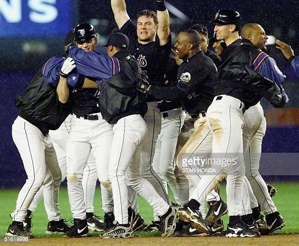 New York Mets Robin Ventura is mobbed by teammates after his hit against the Atlanta Braves in the 15th inning 17 October 1999 during the National...